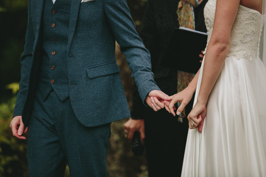 Rebecca and Josh just holding hands during their wedding ceremony at Duneira Estate