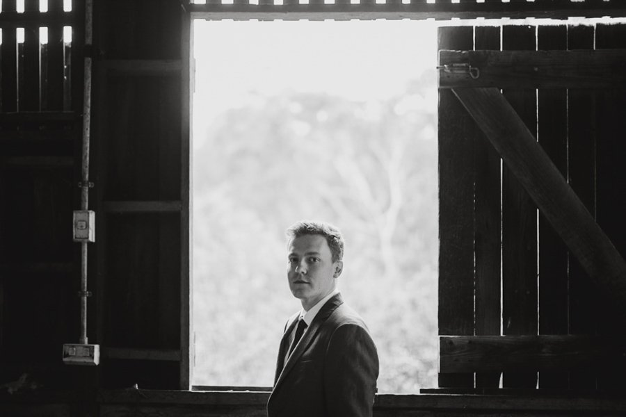 Moody B&W portrait of the groom at Tim & Bridget's Collingwood Children's Farm wedding