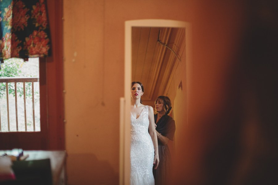 Bride getting dressed, looking in the mirror at her Collingwood Children's Farm wedding