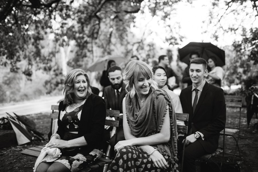 Not deterred by the rain, the bride's family laughs during the ceremony